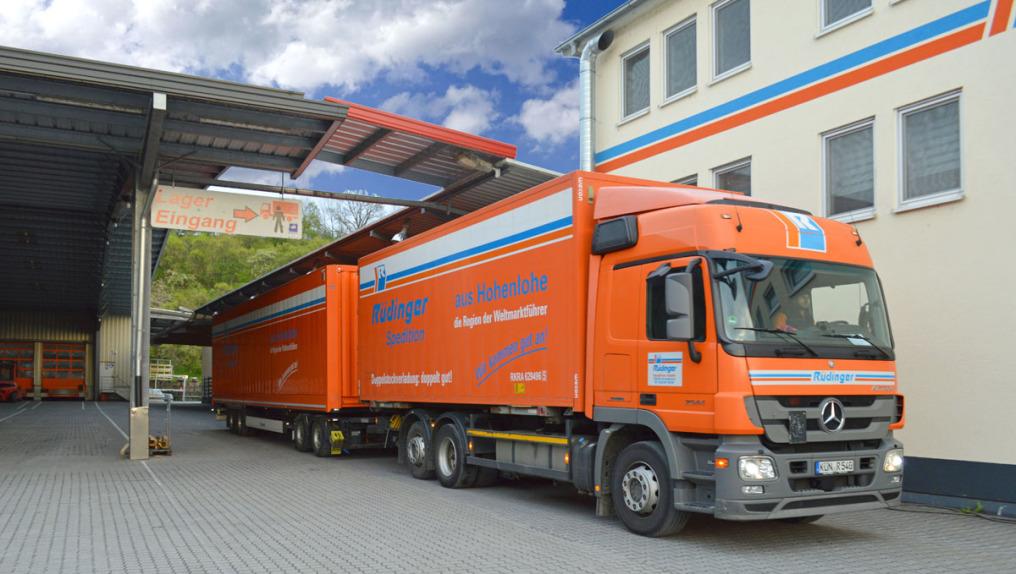 Ein extra-langer Lkw, ein sogenannter Giga-Liner oder Gigaliner steht zwischen einem überdachten Bereich und einem Haus der Spedition. Er ist komplett orange, der Himmel im Hintergrund ist blau mit Wolken.
