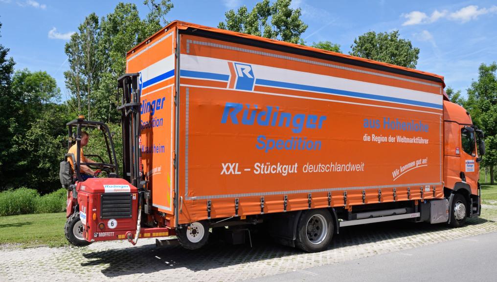 """Ein Planentieflader der Spedition ist von seitlich hinten fotografiert. Er hat einen mobilen Gabelstapler am hinteren Ende und ein Mitarbeiter arbeitet an ihm. Auf dem Lkw steht """"aus Hohenlohe, der Region der Weltmarktführer""""."""