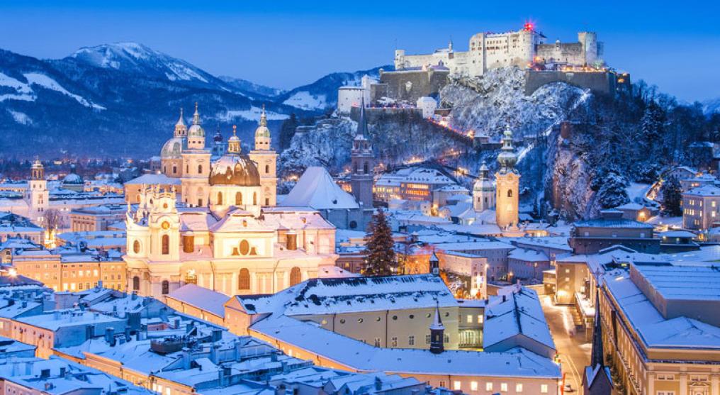 Man sieht eine Nachtaufnahme von Salzburg im Winter. Alles ist schneebedeckt. Auf einem Berg liegt das Schloss, unten ist die große Kirche auffällig. Alle Häuser und Straßen sind hell erleuchtet. Das ganze Bild ist in Blau-Tönen.
