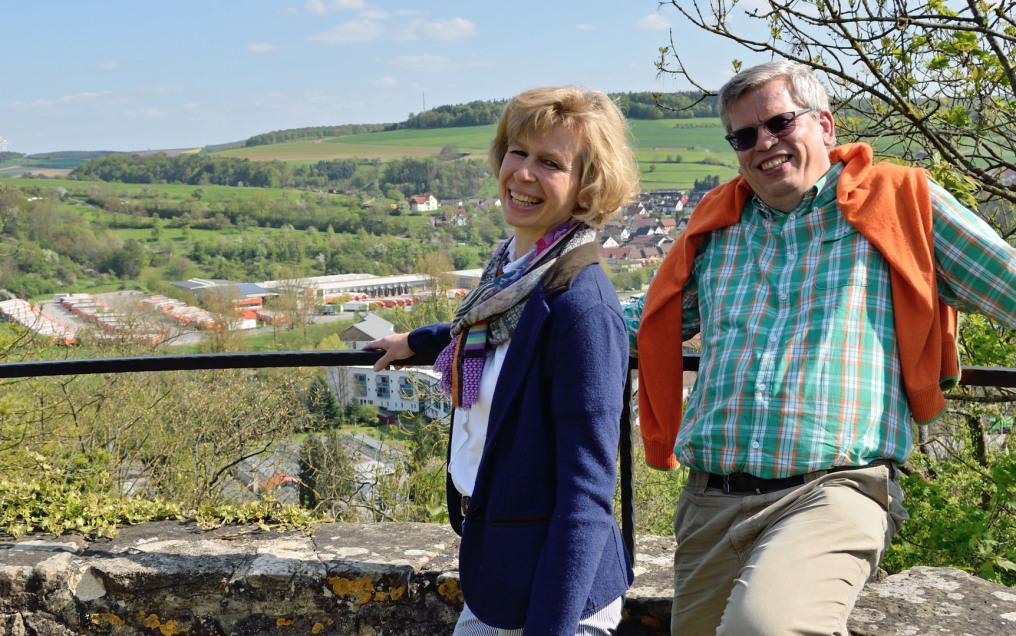 Man sieht Anja und Roland Rüdinger, sie links, protraitartig bis zum Ellenbogen in der Höhe vor einem Ficus Benjamin und einer Glasfront, die orangene Rahmen hat. Beide lächeln in die Kamera.