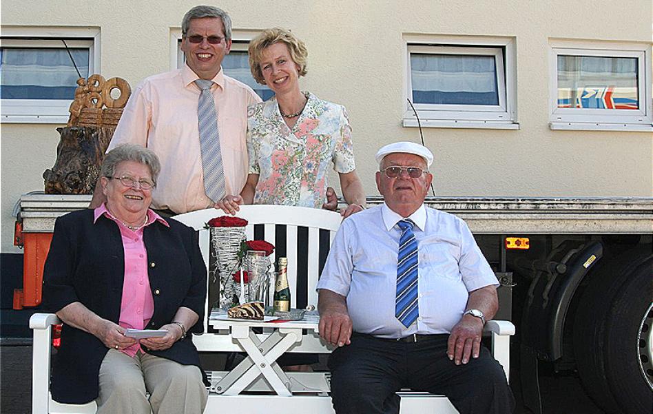 Man sieht die Familie Rüdinger. Vorne sitzen die beiden Eltern von Roland Rüdinger, dahinter steht Roland Rüdinger links und Anja Rüdinger rechts. Im Hintergrund sieht man Fenster eines der Gebäude.