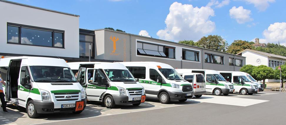 Man sieht 7 Fahrzeuge, davon 6 Transporter, weiß mit grünem Streifen, die mit Fahrtrichtung zum Fotografen nebeneinander stehen. Im Hintergrund ist ein flaches, neues Gebäude.