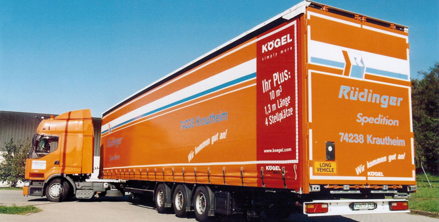 Ein Megasattel-Lkw ist imposant von der Rückseite fotografiert, die Zugmaschine knickt stark ab. Er ist orange und am hinteren Ende ist eine rote Fläche mit besonderen Hinweisen.