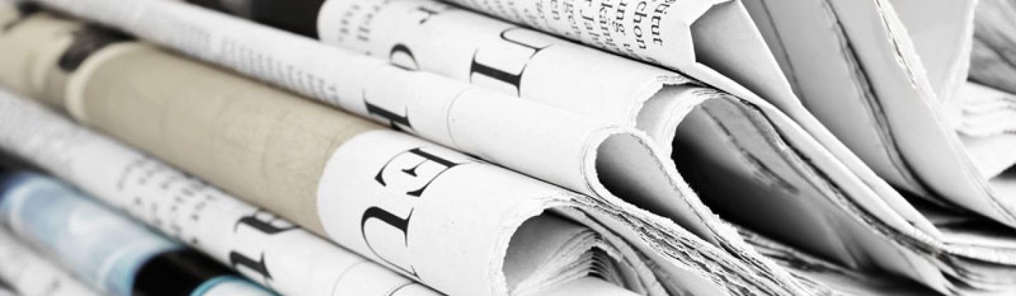 Mehrere Tageszeitungen sind nicht geknickt und nicht gerollt, sondern einmal mittig zusammengelegt, ohne die Rundung zu knicken. Man kann die Titel nicht erkennen.