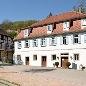 Man sieht das Heimatmuseum in Buchenbach von außen, dahinter grüne Bäume, der Himmel ist blau.