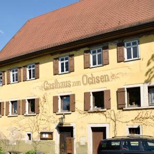 Nahaufnahme des Gasthauses zum Ochsen in Buchenbach Es ist gelb, das Dach ist rot, der Himmel blau.