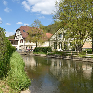 In Heimhausen sieht man im Vordergrund ein stehendes Gewässer. Dahinter sind zwei Fachwerkhäuser. Links sieht man noch einen Baum, der Himmel ist blau und da sind weiße Wolken.