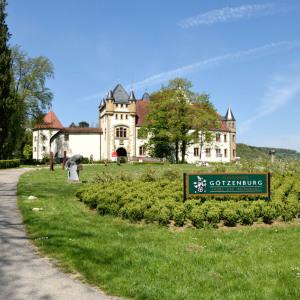 Man sieht die Burg Jagsthausen. Vorne im Rasen steht ein sehr großes Schild, im Rund vor der Burg sind auch Sträucher und es sind Bäume im Bild. Das Wetter ist sonnig.