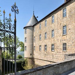 Der Blick geht durch ein historisches Tor auf den Eckturm des Schlosses Waldenburg. Links sieht man das Torgitter, rechts Gebäude.