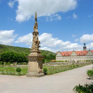 Man sieht das Schloss Weikersheim relativ unbedeutend im Hintergrund. Im Vordergrund ist eine dominierende Steinfigur.