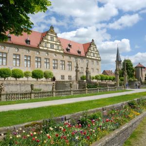 Man sieht Schloss Weikersheim schräg darauf zu fotografiert. Rechts ist ein Rasenstreifen und man sieht schöne Blumen.