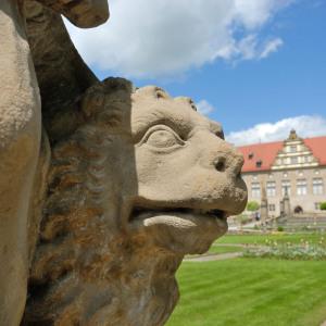 Man sieht einen steinernen Löwen absolut groß fotografiert auf der linken Seite, auf der rechten erkennt man im Hintergrund das Schloss Weikersheim.