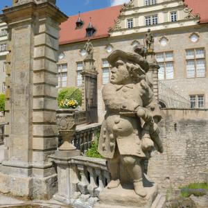 Ein steinerner Gnom steht vor dem Schloss Weikersheim, im Innenbereich des Gartens.