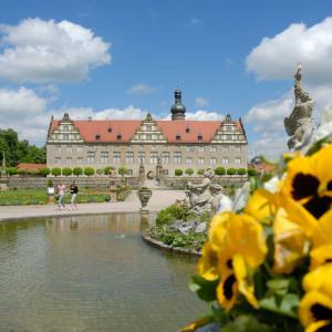 Im Hintergrund ist das Schloss Weikersheim vor blauem Himmel mit weißen Wolken. Im Vordergrund rechts sind dominant gelbe Blumen fotografiert.