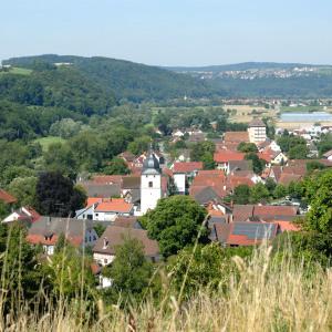 Man blickt von oben auf Dörzbach. Dominant in der Mitte ist der Kirchturm, im Hintergrund sieht man Wald.