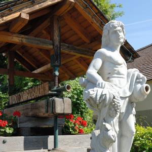 Eine weiße Skulptur hält ein Behältnis und in der Hand Weintrauben.