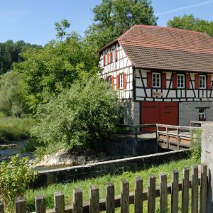 Man sieht eine Fachwerk-Mühle in viel Natur, davor ist ein kleiner Teil eines Zauns fotografiert. Der Himmel ist blau.