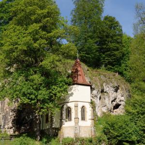 Am Ufer der Jagst ist eine Kapelle direkt an einen Felsen herangebaut. Die Kapelle steht in perfekt grüner Natur.