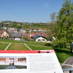 Man blickt auf einen Teil von Osterburken. Im Vordergrund ist eine Informationstafel mit viel Text sichtbar. Dahinter ist mit einem Stahlgestänge ein römisches Fort stilisiert.