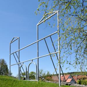 Links fast bildfüllend ist ein Stahlgestänge, das ein römisches Fort stilisiert. Es steht im Rasen, rechts sieht man einen Baum, dahinter Häuser.