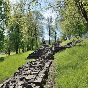 Bergan sieht man in einem parkartigen Gelände im Rasen die untersten riesigen steine von ehemaligen Mauern.