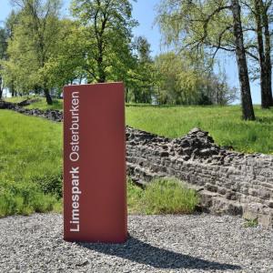 Im Hintergrund sieht man Mauerreste in einer Grünfläche. Im Vordergrund sieht man eine rund 1,5 Meter hohe dicke Stele mit den Worten Limespark Osterburken.