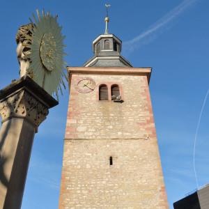 Man blickt einen Kirchturm hinauf, der in den blauen Himmel ragt. Links steht auf einer Säule eine goldene Skulptur mit einem Sonnensymbol.