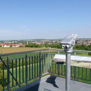Man schaut über das Geländer des Aussichts-Bauwerkes und sieht in der Ferne Öhringen. Dahinter weitere Hügel. Zentral in der Mitte ist ein stationäres Fernsichtgerät in grauem Metall.