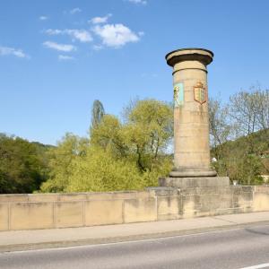 Auf einer historischen Brücke steht eine sehr mächtige Säule mit spannenden Inschriften. Im Hintergrund sind Bäume mit hellgrünen Blättern, am blauen Himmel sind wenige Wolken. Die Sonne scheint.