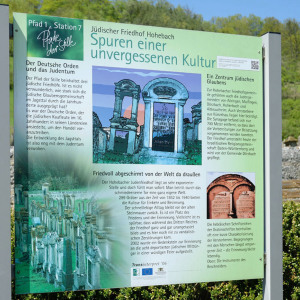 """Man betrachtet das Hinweisschild an einem jüdischen Friedhof, es ist bildfüllend und es trägt den Titel """"Spuren einer unvergessenen Kultur""""."""