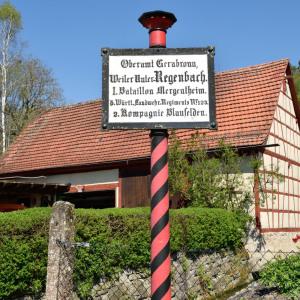 Man sieht auf eine historische Tafel, deren Stange rot/schwarz geringelt nach oben verläuft. Die Tafel selbst ist schwarz auf weiß beschrieben in altdeutscher Schrift. Dahinter ist ein Fachwerkhaus.