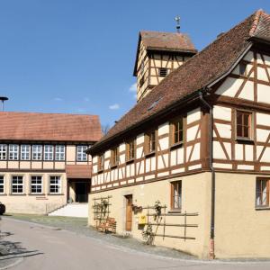 Man sieht zwei dekorative Fachwerkhäuser. Links ist eine Straße, der Himmel ist blau.