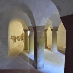 Man sieht die Verstrebungen einer kleinen Krypta, sowie den Schattenwurf der Säulen durch das Blitzlicht.