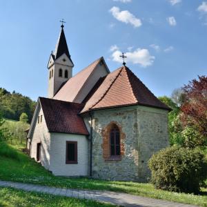Man sieht eine Kirche eingebettet in der Natur, ohne Häuser. Der Kirchturm ist hinter dem Schiff, der Himmel ist blau und man sieht weiße Wolken.