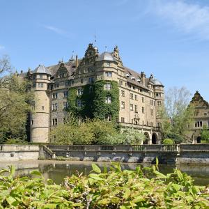 Man sieht das Schloss Neuenstein inmitten eines Sees. Ein Eckturm ist heftig mit Efeu bewachsen, eine Brücke führt über das Wasser.