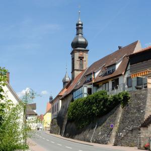 Man schaut auf eine Straße, die zum Bildhintergrund führt. Auf der rechten Seite steht auf einer Anhöhe, hinter einer Mauer eine Kirche, von der man den Turm sieht. Der Himmel ist blau.