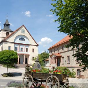 Im Vordergrund steht ein historischer Wagen eines Pferdefuhrwerks, der mit Blumen geschmückt ist. Dahinter sieht man links die Kirche, rechts ein Gemeindehaus.