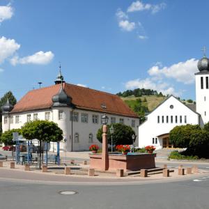 Vor einem rötlichen Stadtbrunnen in Unterschüpf sieht man links eine Art Schloss und rechts eine Kirche. Der Himmel ist blau mit weißen Wolken.