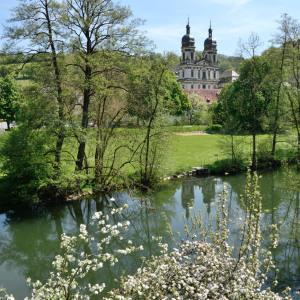 Man sieht das Kloster Schöntal über ein Gewässer hinweg. Davor ist viel Natur, es ist bestes Wetter.