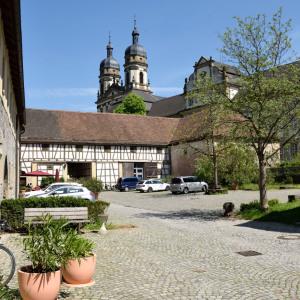 Man ist im Innenhof von Kloster Schöntal. Links sind zwei Terrakotta-Töpfe, in der Mitte zwei Klostertürme, rechts ein Baum.