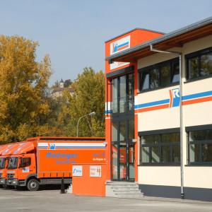 Links im Bild sieht man eine Reihe kleiner Lkw, rechts das neue Verwaltungsgebäude der Spedition.