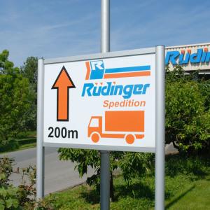 Bildfüllend weist ein Schild zur  Spedition hin. Die Farben sind natürlich orange und hellblau.