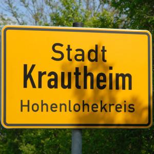 """Ein Ortseingangsschild ist bildfüllend bei Sonne fotografiert. Im Hintergrund ist Natur, auf dem Schild steht """"Krautheim Hohenlohekreis""""."""