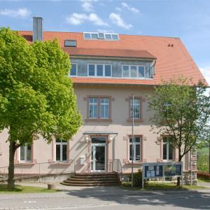 Im Bild sieht man das Rathaus von Krautheim bildfüllend. Vorne sind zwei Bäume mit frischen Blätter, davor ist geteert. Im Hintergrund sieht man blauen Himmel mit weißen Wolken.