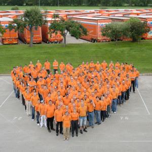 Etwa 50 bis 70 Mitarbeiter bilden ein Herz, dahinter ist ein breiter Grasstreifen, weiter hinten steht Jumbo-Lastzug neben Jumbo-Lastzug.