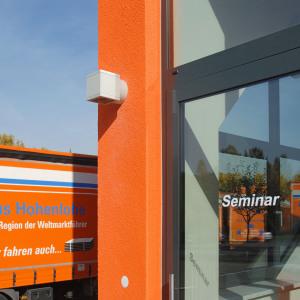 """Man sieht ein großes Schild mit dem Wort """"Seminare"""" auf dem orangenen, modernen, neuen Verwaltungsgebäude der Spedition."""