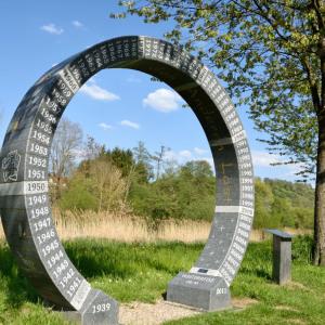 In einem Grünbereich steht ein Kunstwerk. Es ist ein etwa 3 Meter hoher stabiler Ring aus Metall in den Verschiedenes eingraviert ist.