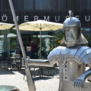 Man sieht auf die Figur eines Römers in Lebensgröße mit seiner silbernen Rüstung und einer Lanze in der Hand. Er steht vor gelben Schirmen vor dem Römer-Museum in Osterburken.