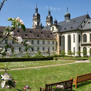 Man blickt auf die Außenansicht von Kloster Schöntal, allerdings von innerhalb der Klostermauern. Rechts vorne sind Bänke, und zwischen dem Betrachter und dem Gebäude ist eine parkartige Wiese und dort sind Gewächse.