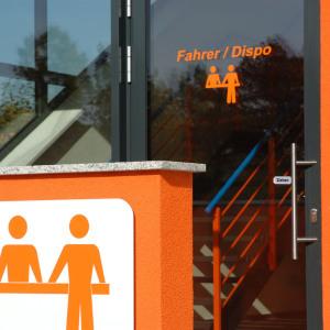 """Man blickt auf die Glastür des Verwaltungsgebäudes der Spedition. In orangener Schrift liest man dort """"Fahrer / Dispo""""."""